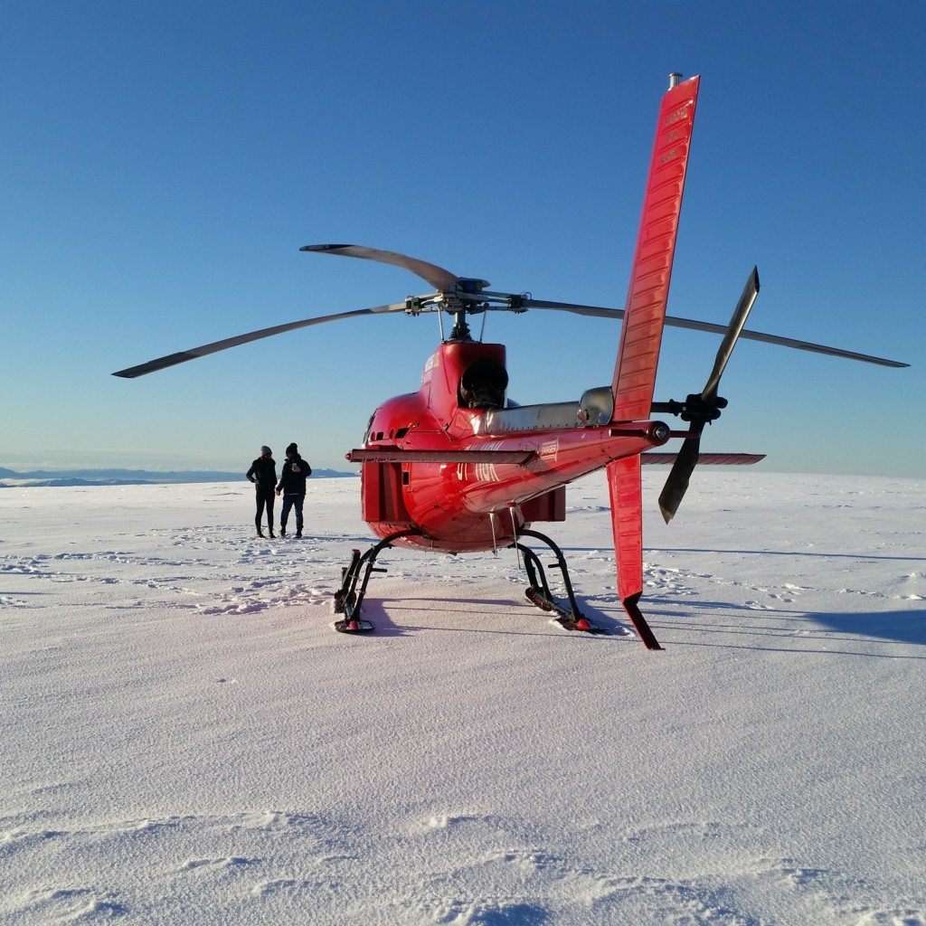 Astar helicopter on a Reykjavik summit with two passengers enjoying the view.