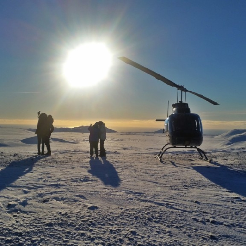 Taking pictures on the Reykjavik summit tour, next to one of our helicopters