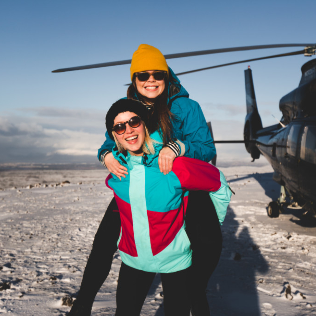 Happy people on a mountain summit helicopter tour in Reykjavik